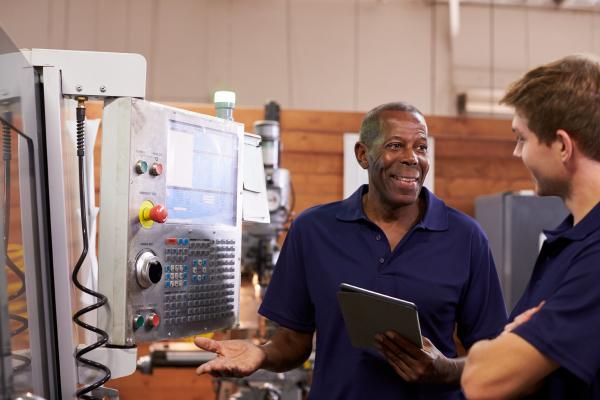 engineer-training-male-apprentice-on-cnc-machine