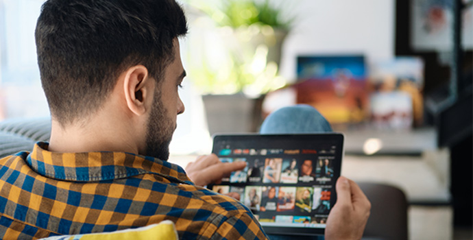 man-choosing-movie-for-streaming-on-tablet